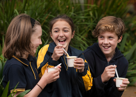 School kids eating tubs of yoghurt