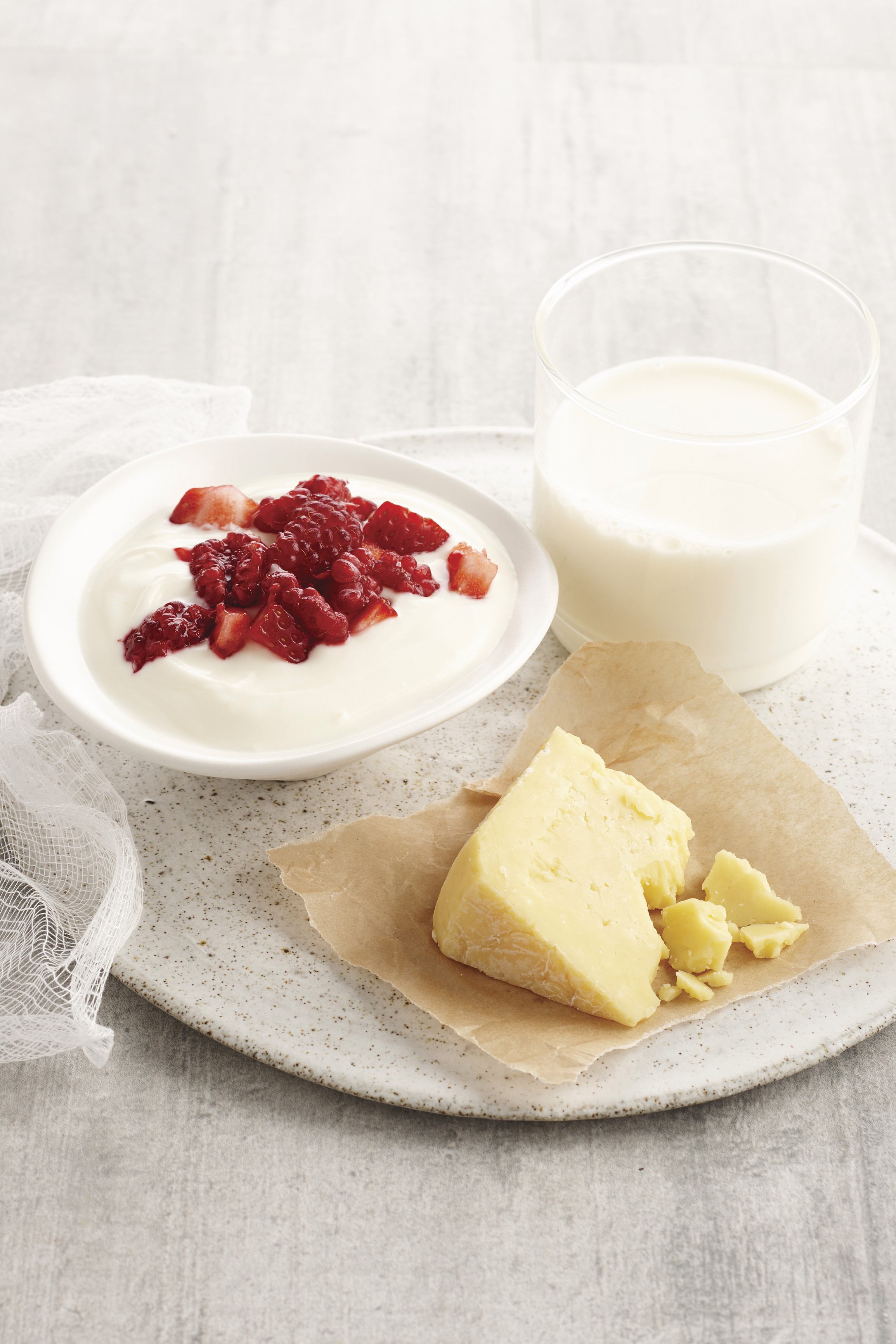 Wedge of cheese, glass of milk and bowl of yoghurt and berries