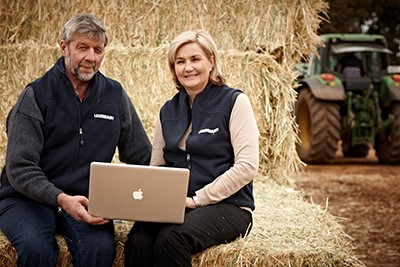 Two dairy farmers using a laptop on their farm