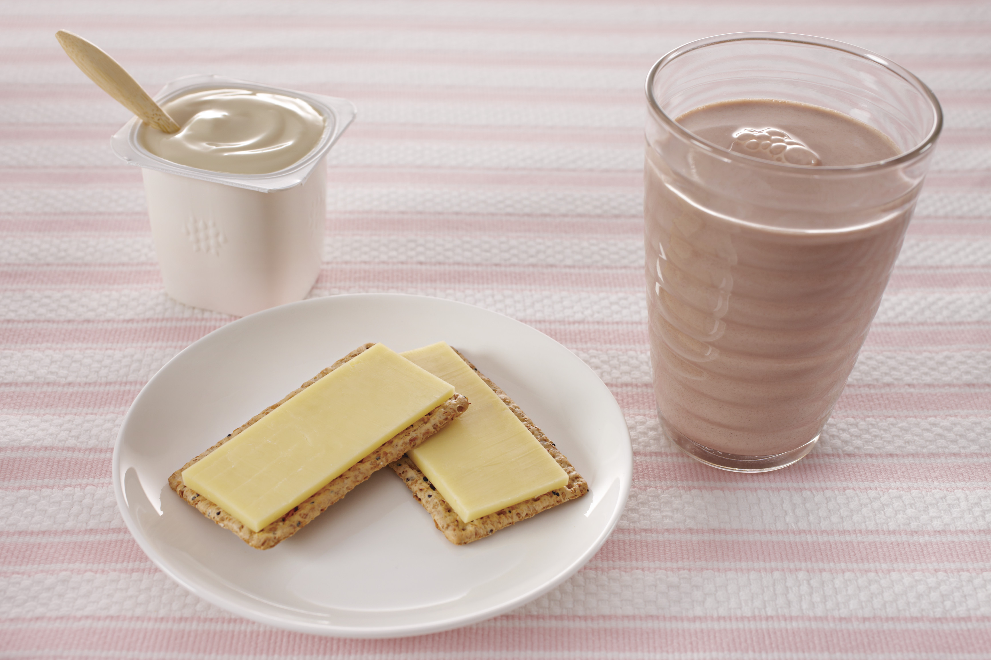 Plate of cheese and crackers, glass of chocolate milk and tub of plain yoghurt